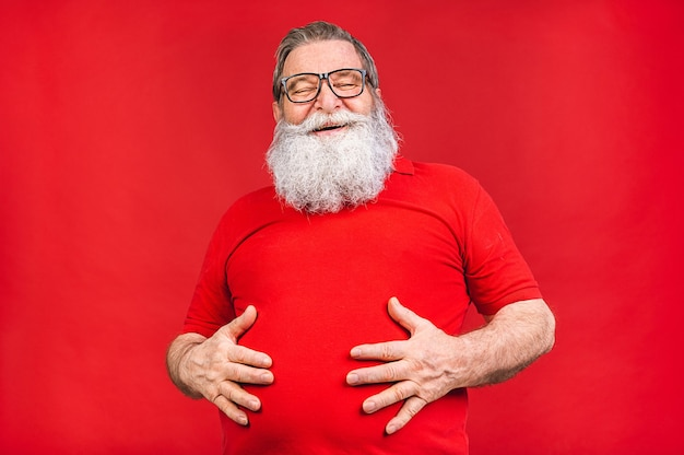 Viejo barbudo con gafas en camiseta roja aislado sobre fondo rojo.