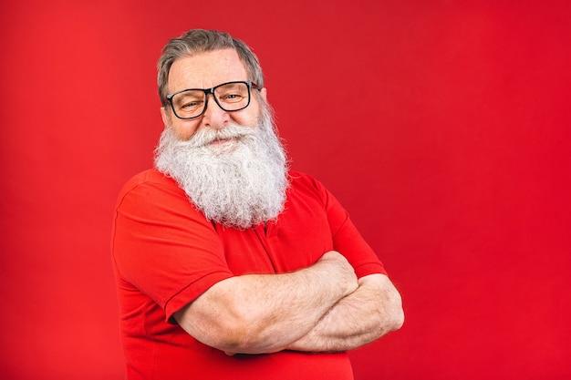 Viejo barbudo con gafas en rojo thisrt aislado sobre fondo rojo.