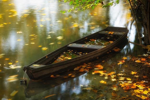 Viejo barco de madera en el lago en otoño