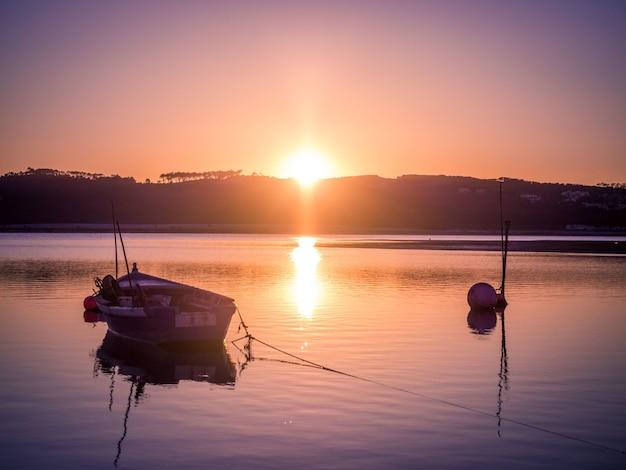 Viejo barco de pesca en el río con la impresionante vista de la puesta de sol