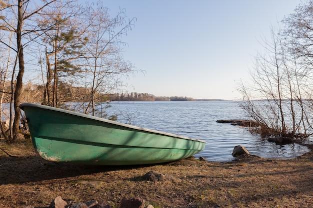 Viejo barco verde en la costa del lago