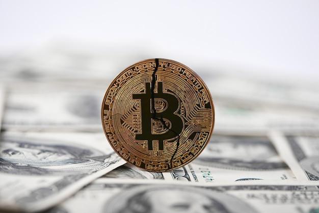 Viejo bitcoin roto en billetes de dólar