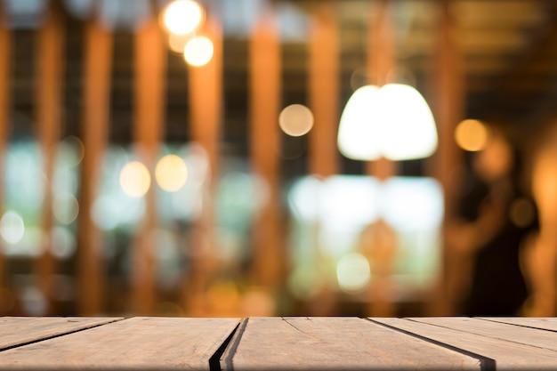 Viejo blanco de la tabla de madera del vintage delante del fondo borroso del restaurante