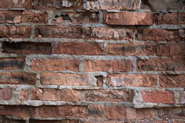 Viejo capeado de ladrillos de textura rugosa