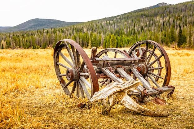 Viejo, carro de madera vintage abandonado y roto en un prado dorado en colorado