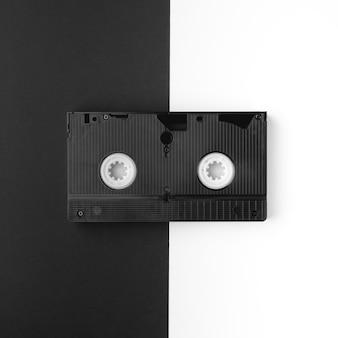 Un viejo cassette vhs se encuentra horizontalmente sobre una mesa en blanco y negro dividida por la mitad