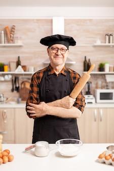 Viejo caucásico vistiendo delantal en la cocina de casa sonriendo