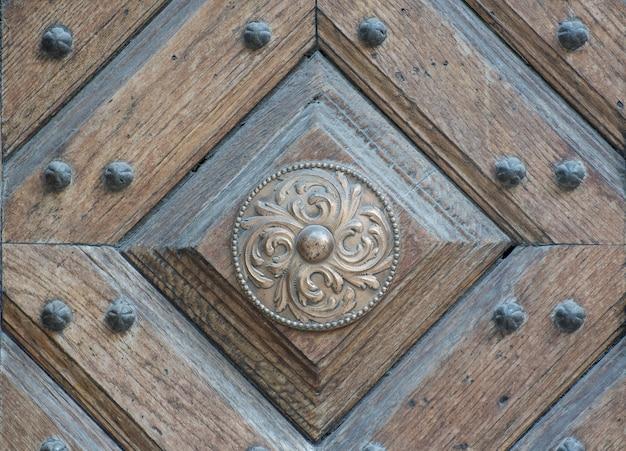 Viejo círculo de bronce en mal estado con un hermoso adorno sobre un fondo de puerta de madera
