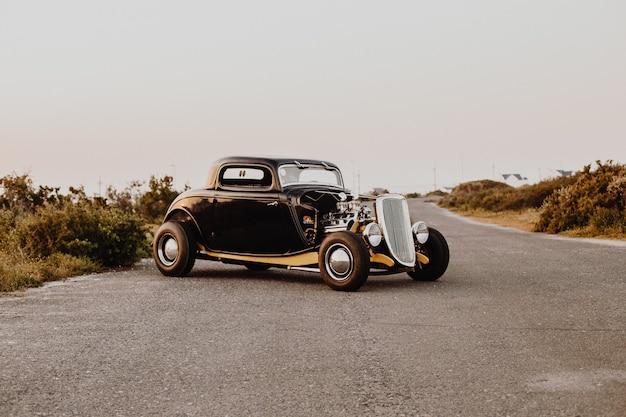 Viejo coche antiguo estacionado en medio de la carretera de la autopista