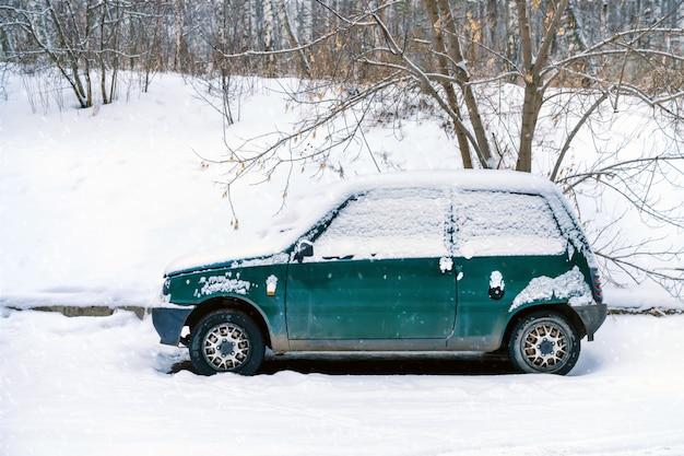 Viejo coche verde abandonado viejo cubierto de nieve sembrada. estacionado al borde del bosque en invierno