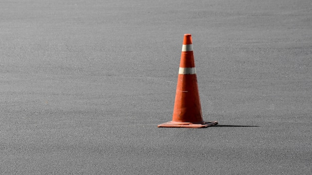 Viejo cono de tráfico naranja en la carretera de asfalto