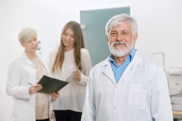 Viejo doctor confiado que permanece delante de ayudante y del paciente.