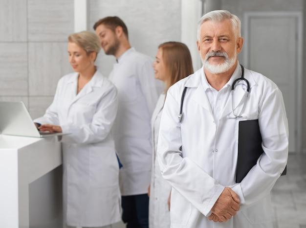 Viejo doctor posando, personal médico de pie detrás.