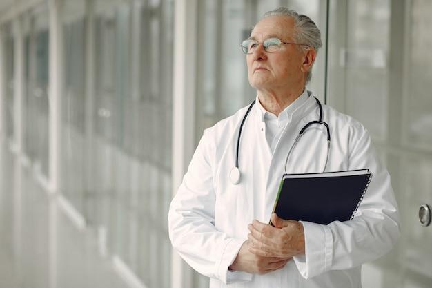 Viejo doctor en uniforme de pie en el pasillo