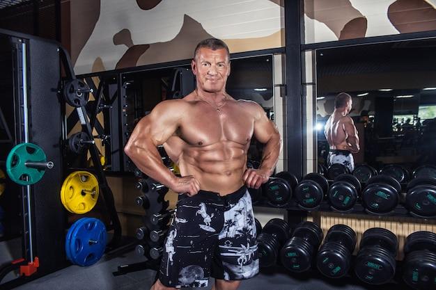 El viejo está en el gimnasio cerca de las pesas, entrenando.