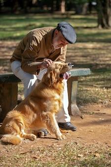 Viejo hombre acariciando un perro golden retriever