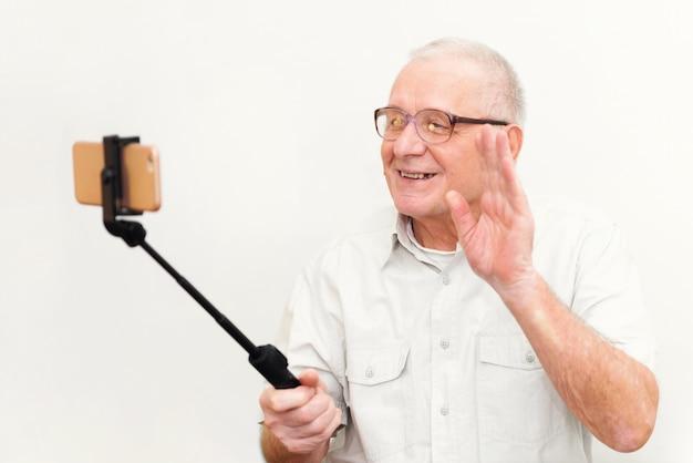 Viejo hombre activo que toma el selfie con el teléfono móvil aislado en concepto gris del blogger de vlogger del fondo