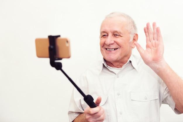 Viejo hombre activo que toma el selfie con el teléfono móvil aislado en fondo gris