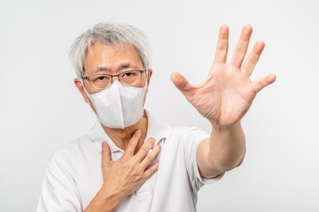 Viejo hombre asiático con máscara n95 extendiendo su mano izquierda con estiramiento de palma pidiendo ayuda con su mano derecha tocando su pecho