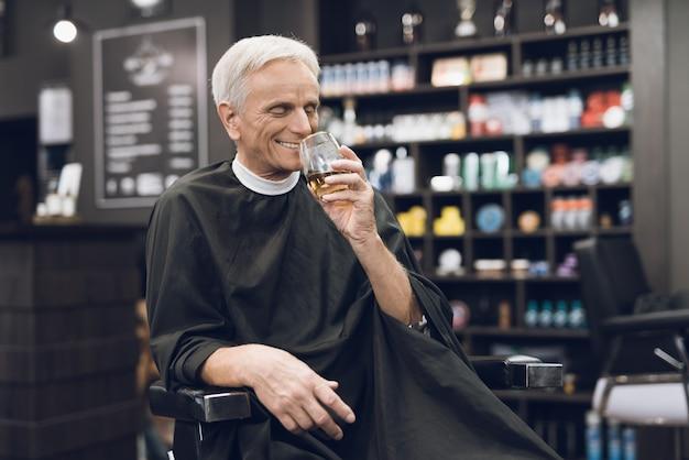 Viejo hombre bebe alcohol en la silla de barbero en la barbería.
