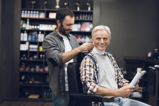 Viejo hombre con canas se sienta en estilista en peluquería.