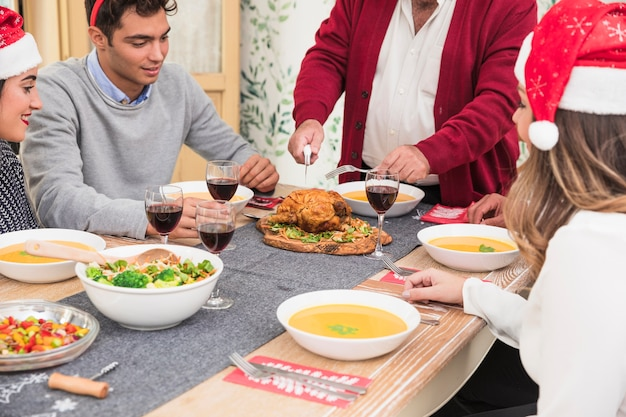 Viejo hombre cortando pollo al horno en la mesa de navidad