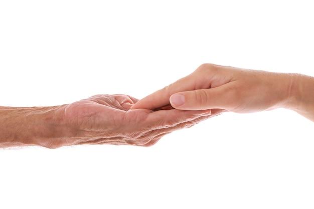 Viejo hombre y mujer joven manos sobre fondo blanco.