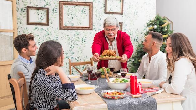 Viejo hombre poniendo pollo al horno en mesa festiva