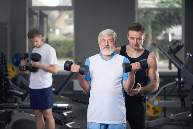 Viejo hombre posando con pesas, entrenamiento de entrenador.
