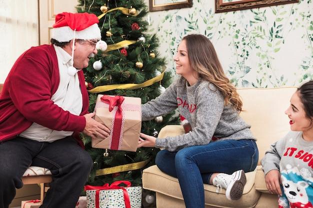 Viejo hombre que da la caja de regalo a la mujer joven
