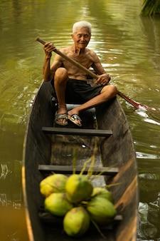 Viejo hombre que recoge el coco usando el barco en la granja del cococut