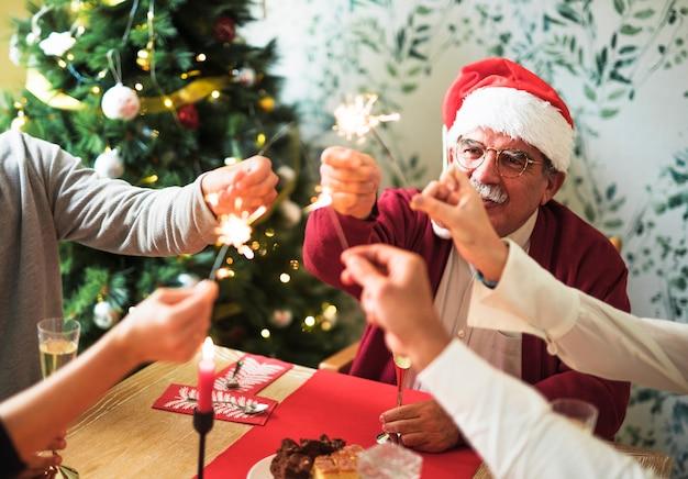 Viejo hombre que sostiene el fuego de bengala en la mesa festiva con la familia