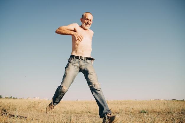 Viejo hombre saltando en un campo de trigo