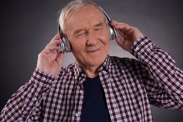 Viejo hombre satisfecho que escucha la música en los auriculares.