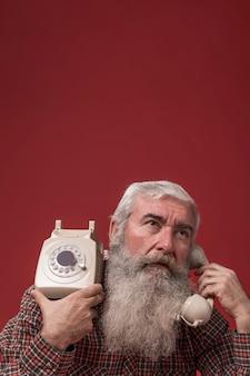 Viejo hombre sosteniendo un teléfono