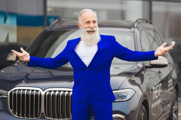 Viejo hombre styish de pie cerca del automóvil de lujo. hombre rico maduro en el traje al aire libre cerca del coche.
