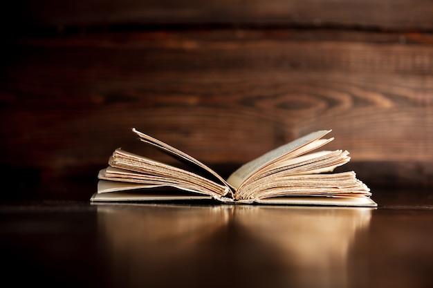 Viejo libro abierto sobre la mesa de madera. vista lateral