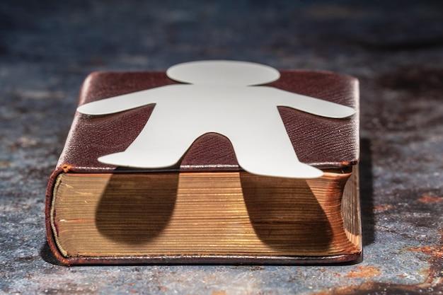 Un viejo libro con la silueta de un hombre acostado, hecho de papel. marcador.