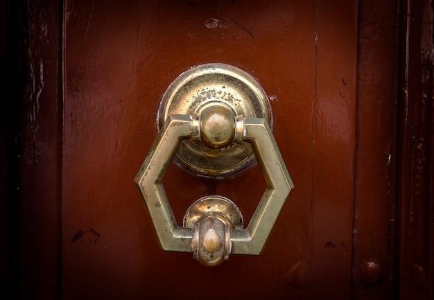 Viejo martinete de la manija de la puerta de metal en una madera rugosa