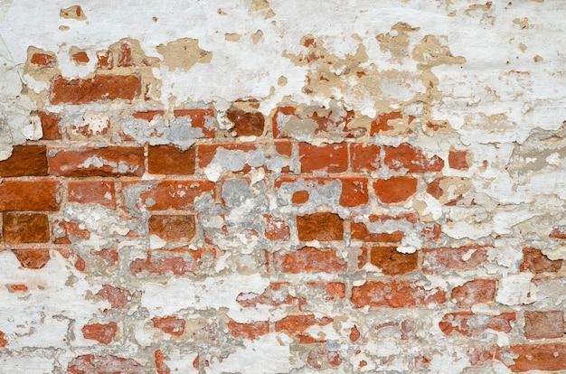 Viejo muro de ladrillo desgastado rojo con pedazos de encalado, masilla y yeso de fondo