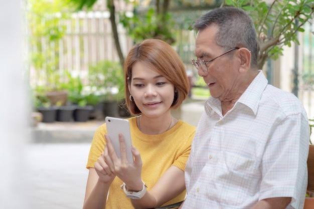 Viejo padre asiático y su hija. hija le enseña a un padre anciano a usar un teléfono móvil