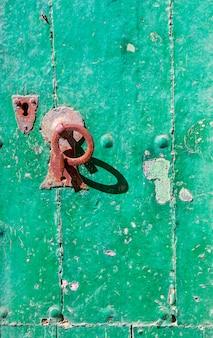 El viejo pomo de puerta verde de madera
