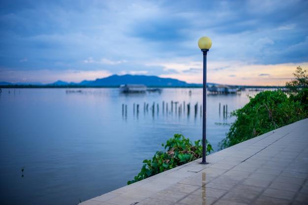Viejo poste amarillo de la luz de calle en la calzada cerca del lago con la visión borrosa.