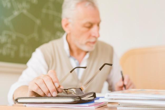 Viejo profesor haciendo notas en cuaderno