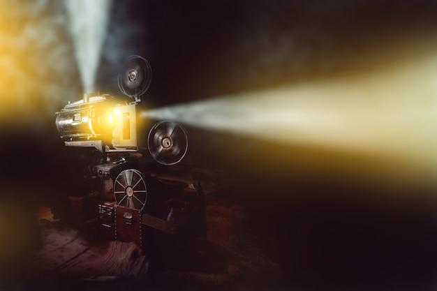 Viejo proyector de película con humo en el fondo oscuro de la habitación