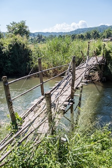 Viejo puente de bambú está cruzando el pequeño río.