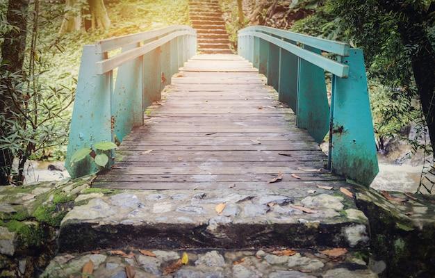 Viejo puente de madera con puente verde para cruzar arroyos