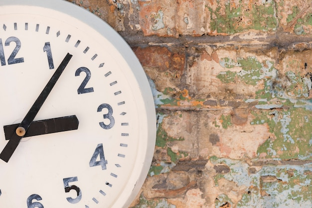 Un viejo reloj blanco contra la pared desgastada.