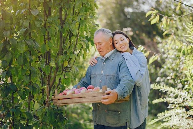 Viejo senior de pie en un jardín de verano con cosecha
