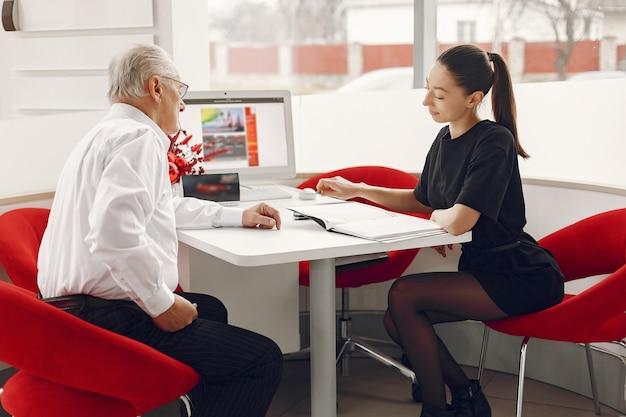 Viejo sentado en un salón del automóvil y hablando con el gerente